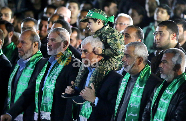 The son of Hamas official, Mazen Faqha, who was shot dead by unknown gunmen sits on the shoulders of Yahya Sinwar, the new leader of Hamas in the Gaza Strip during a memorial service in Gaza city on March 27, 2017. Photo by Ashraf Amra