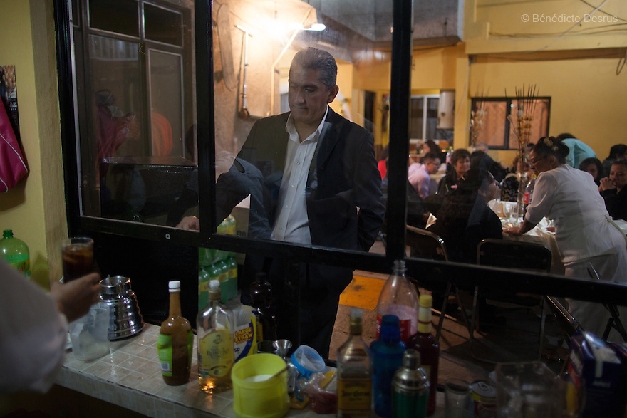"Donovan orders a drink at the wedding party of his sister-in-law in Iztapalapa, Mexico on October 31, 2015. Donovan Tavera, 43, is the director of ""Limpieza Forense México"", the country's first and so far the only government-accredited forensic cleaning company. Since 2000, Tavera, a self-taught forensic technician, and his family have offered services to clean up homicides, unattended death, suicides, the homes of compulsive hoarders and houses destroyed by fire or flooding. Despite rising violence that has left 70,000 people dead and 23,000 disappeared since 2006, Mexico has only one certified forensic cleaner. As a consequence, the biological hazards associated with crime scenes are going unchecked all around the country. Photo by Bénédicte Desrus"