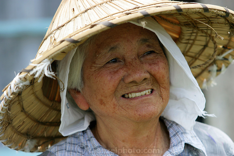 """90-year-old Haruko Maeda, in the front yard of her home in Ogimi Village, taking a break from cutting her lawn with a pair of hand shears. """"I'm getting this done before it gets too hot,"""" she explains. Hara hachi bu: """"eat only until 80 percent full,"""" say older Okinawans. The island has been the focus in recent years of researchers trying to discover why a disproportionately large number of Okinawans are living to age 100 or more. (Supporting image from the project Hungry Planet: What the World Eats)"""