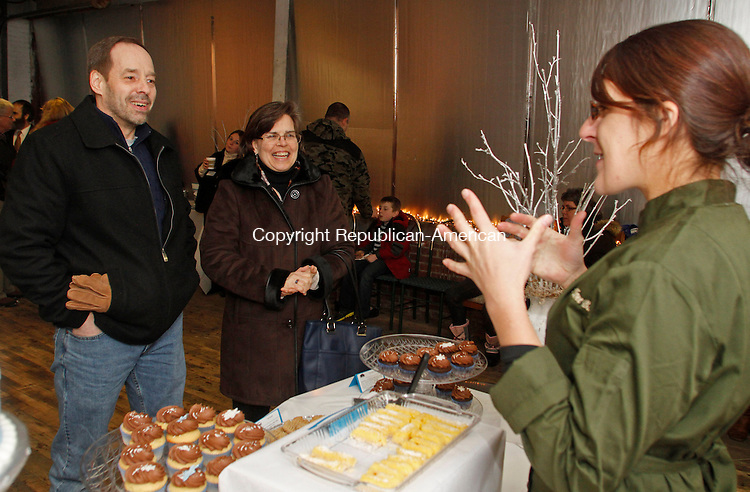Winsted, CT-012514MK01 Katie Sosnicki co-owner of the Willow Tree Bakery describes some of the bakery items to John and Beth Duffy, from Harwinton, during an open house at the the former Capitol Products kitchen supply factory in Winsted on Saturday night. Forty-five people braved the snow and cold temperatures to enjoy the baked goods. Former Selectman Michael J. Renzullo is the executive director and founder of Laurel City Revamp, a nonprofit that aims to rehabilitate old downtown mill buildings. Renzullo gave tours of the building he owns and is renovating which when finished the Willow Tree Bakery will be his first tenant.  Michael Kabelka / Republican-American