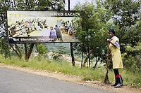 "Rwanda. Southern province. Gitarama. District of Muhanga. A black woman sweeps up dirt on the side of the concrete road. Giant advertisement board for the Gacaca jurisdiction. The Gacaca (pronounced ""gachacha"") court is part of a system of community justice inspired by tradition and established in 2001 in Rwanda, Rwanda implemented the Gacaca court system, which has evolved from traditional cultural communal law to enforcement procedures and prison condemnation. © 2007 Didier Ruef"