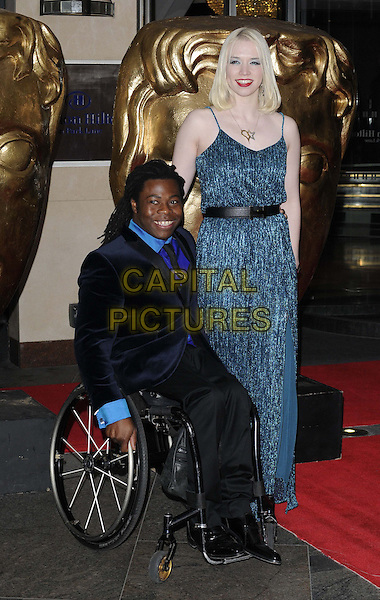 Ade Adepitan & guest.attended the British Academy ( BAFTA ) Video Game Awards, London Hilton Park Lane Hotel, London, England..March 5th, 2013.full length black shirt tie suit wheelchair belt blue dress  .CAP/CAN.©Can Nguyen/Capital Pictures.
