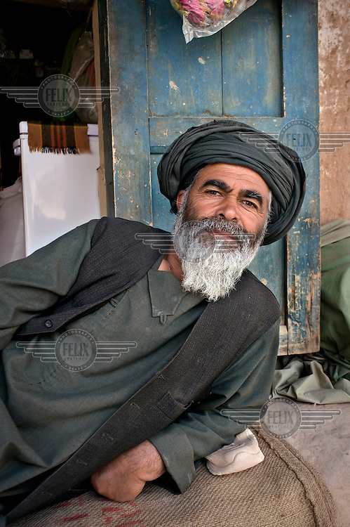 A salesman rests in front of his shop.