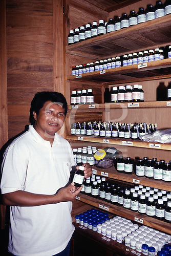 Altamira, Para State, Brazil. Green Pharmacy medicinal plant garden. Chemist taking out a bottle from the extract stock.