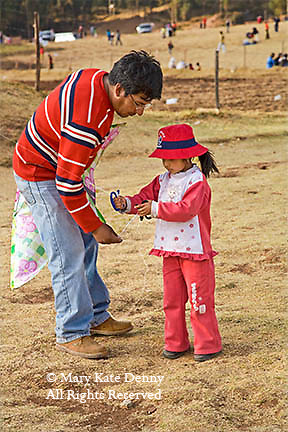 Male Peruvian assists his female five year old child with the string on her kite