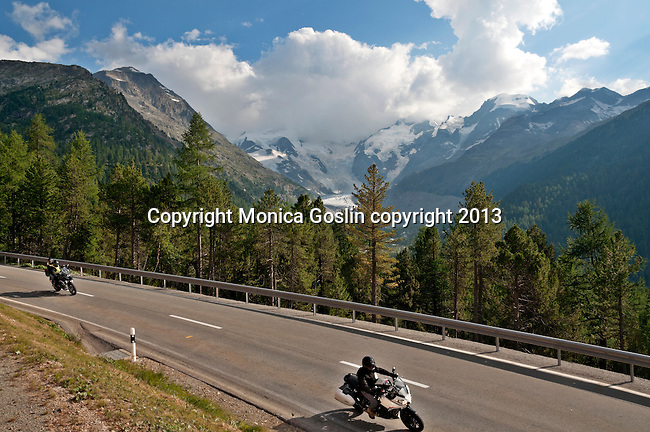 The Bernina Express runs next to the highway and crosses the highway at some points. Here you can see motorcyclists with the Piz Bernina in the background, which is the highest mountain of the Eastern Alps at 4,049 meters; The Bernina Express is the highest altitute transalpine railway and one of the steepest railways