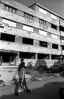 Mostar, due giovani davanti a un edificio in rovina danneggiato durante la guerra, con fori di proiettile nel muro --- Mostar, two youngsters passing by the ruin of a building damaged during the war, with bullet holes in the wall