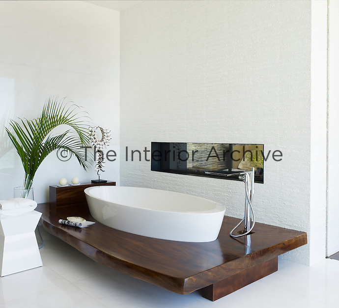 A stylish bathroom features a luxurious shell-shaped Rifra tub.