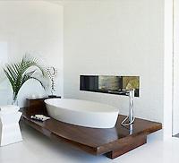 A stylish bathroom features a luxurious shell-shaped Rifra tub.