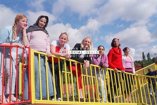 Multiracial group of girls leaning over coloured railings in children's playground,