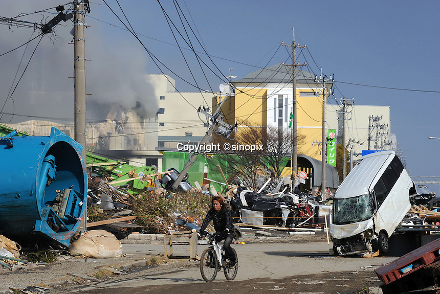 A man passes in front of devastation caused by the Japanese earthquake in Sendai, Japan. One of the biggest earthquakes ever recorded struck off the coast of Japan on 11 Mar 2011 had killed thousands of people. The death toll was expected to rise dramatically, with tens of thousands reported missing..13 Mar 2011....