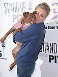 Kaley Cuoco-Sweeting poses with Georgia, an adoptable pup from Orange County Pitbull Rescue at the The 4th Annual Stand Up for Pits event at the Hollywood Improv in West Hollywood, California on November 02,2014                                                                               © 2014 Hollywood Press Agency