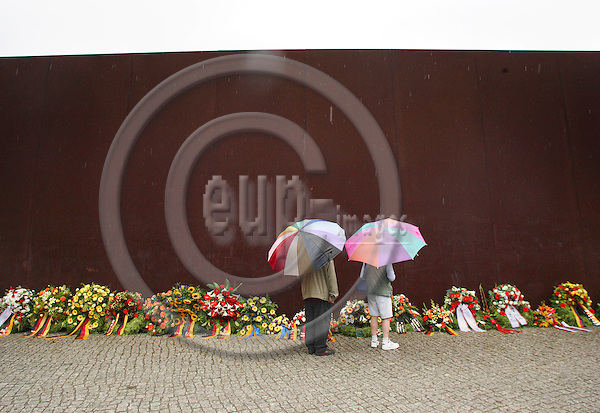 BERLIN - GERMANY 13.  AUGUST 2006 -- At the 45th Anniversary of the Construction of the Berlin Wall,poeple look at the flowers by the formal Berlin Wall Memorial at Bernauer Strasse -- PHOTO: UFFE Noejgaard/ EUP-IMAGES