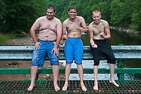 Three young man who were jumping off a bridge into the river underneath flexing muscles and looking tough.