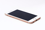 Rose gold, pink white Apple iPhone 6s with blank black screen lying isolated on white background
