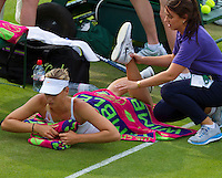 26-06-13, England, London,  AELTC, Wimbledon, Tennis, Wimbledon 2013, Day three, Maria Sharapova (RUS) gets injury treatment after she fell on the grass<br /> <br /> <br /> <br /> Photo: Henk Koster