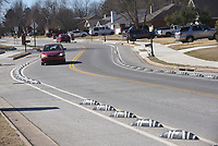 NWA Democrat-Gazette/FLIP PUTTHOFF <br /> Vehicles move Saturday March 16 2019 along Dick Smith Street in Springdale between barriers installed to create two bike lanes.