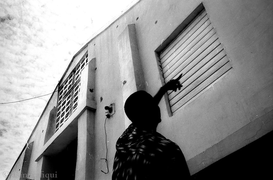 a cite soleil resident points to the walls of a church damaged by MINUSTAH machine gun fire<br />