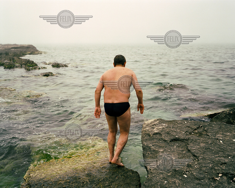 A man tiptoes into the water on the Caspian Sea coast.