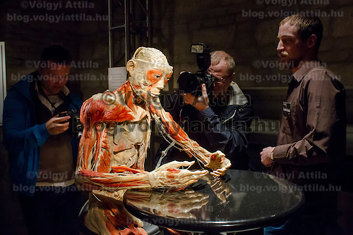 Photographer takes a photo of a preserved human body on display at an exhibition in Budapest, Hungary on April 02, 2012. ATTILA VOLGYI