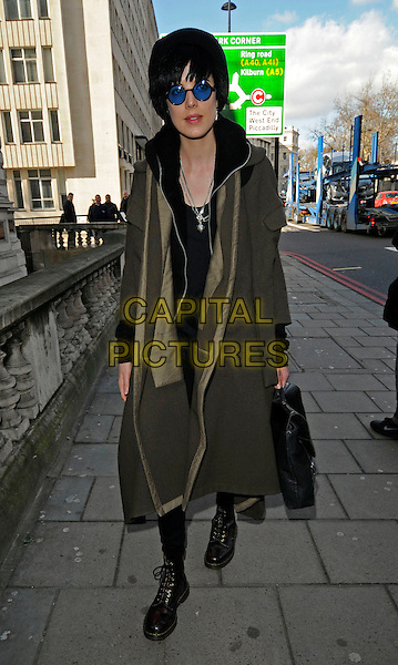 AGYNESS DEYN.At the MAC cosmetics VIVA GLAM Launch Event at Il Bottaccio, Grosvenor Place, London, March 1st 2010..full length round blue tinted glasses sunglasses black boots lace-up green khaki coat bag silver necklaces dms dm walking .CAP/CAN.©Can Nguyen/Capital Pictures.
