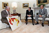 United States President Ronald Reagan, center, and U.S. Vice President George H.W. Bush, right, review a map showing drought severity with U.S. Secretary of Agriculture Richard Lyng, left, in the Oval Office on Friday, June 17, 1988..Mandatory Credit: Bill Fitz-Patrick - White House via CNP