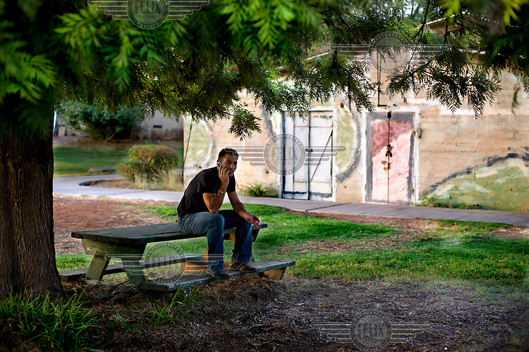 A man smokes and talks on a mobile phone at the Afikim kibbutz. /Felix Features