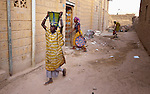 While other women go about their work, a woman carries a bucket of water along a street in Timbuktu, the northern Mali city that was seized by Islamist fighters in 2012 and then liberated by French and Malian soldiers in early 2013. During the jihadis' rule, girls and women could not appear in public unless they were completely covered.