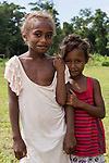 Peava Village, Gatokae Island, Solomon Islands; two young girls pose for a photo in the field by their school house