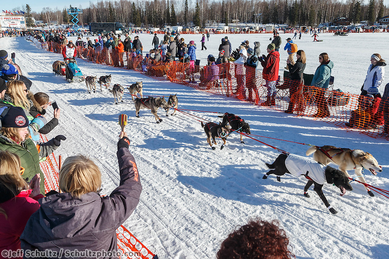 Kristin Bacon runs down the start chute lined with spectators during the Ceremonial Start of the 2016 Iditarod in Willow, Alaska.  March 06, 2016