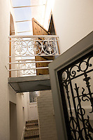 A walkway links the old part of the house to a new extension; the wrought-iron guardrails were found in a flea-market