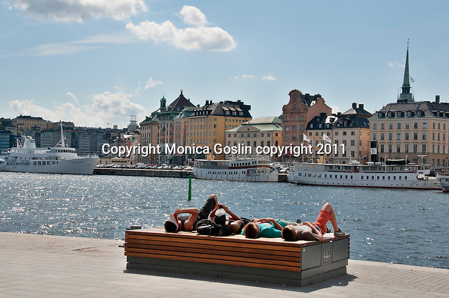 Four kids soak up some sun between sight seeing in Stockholm, Sweden