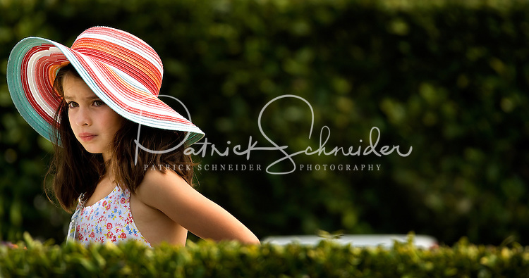 A young girl in a wide brim hat watches the horse races during the Queen's Cup Steeplechase in Mineral Springs, NC.