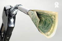 One US banknote coming out petrol pump nozzle (Licence this image exclusively with Getty: http://www.gettyimages.com/detail/sb10068346ar-001 )
