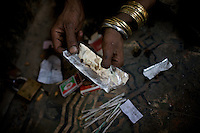 A heroin addict prepares a dose of heroin to be smoked on the second floor of a depot in front of a Mosque  in the city of Rawalpindi, Pakistan on Thursday November 27 2008.///..While Bangladesh, India, Nepal and Maldives all suffer from drug consumption, Pakistan is the worst victim of the drug trade in South Asia. Today, the country has the largest heroin consumer market in the south-west Asia region..The drug addicts resort to crime for generating income for the purchase of narcotics. The situation is becoming serious due to the number of heroin addicts in the country. An alarming rate of increase of 100,000 addicts per year is highly dangerous to society. The drug addicts are affecting nearly 20 million dependents and family members with psychological, social, and economic repercussions.