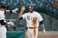 Rice Owls designated hitter Michael Aquino #15 is greeted by a teammate after scoring a runAA during the NCAA baseball game against the North Carolina Tar Heels on March 1st, 2013 at Minute Maid Park in Houston, Texas. North Carolina defeated Rice 2-1. (Andrew Woolley/Four Seam Images).