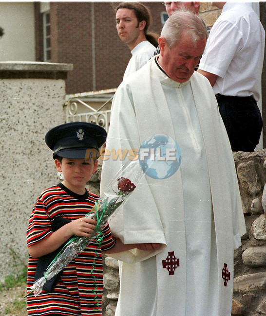 Conor Mooney (8) carries a red rose and wears his fathers Aircorp hat as he walks along with former Army chaplin Monsenior Edward Dunne in front of his father Patrick's funeral in Stamullen Co.Meath..Pic Fran Caffrey / Newsfile
