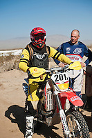 201x motorcycle rider Derek Duncan arrives at Honda pit #2 at race mile 70, 2012 San Felipe Baja 250, San Felipe, Baja California, Mexico.