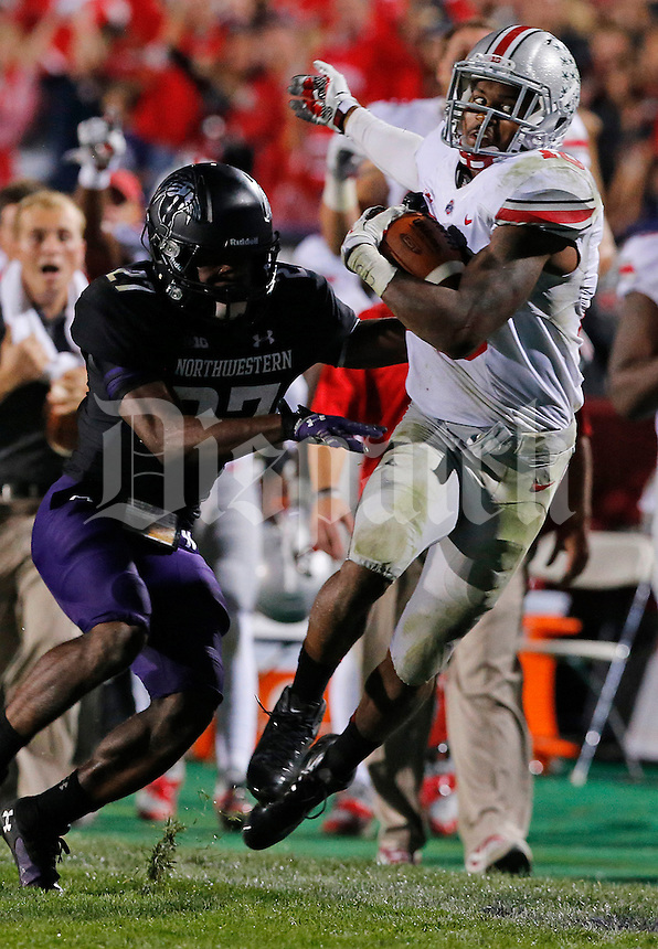 Ohio State Buckeyes quarterback J.T. Barrett (16) is pushed into the sidelines by Northwestern Wildcats cornerback Matthew Harris (27) in the fourth quarter of their game at Ryan Field in Evanston, IL on October 5, 2013. Columbus Dispatch photo by Brooke LaValley)