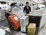 January 24, 2017, Narita, Japan - Japan Airlines (JAL) ground staff wearing a robot suit Hybrid Assistive Limb (HAL), developed by Tsukuba University professor Yoshiyuki Sankai and Cyberdyne demonstrates to carry a heavy baggage at the JAL check-in counter as airline companies started their field tests of HAL at the Narita International Airport in Narita, suburban Tokyo on Tuesday, January 24, 2017. The HAL is designed to learn the user's motion and assist their movements, can be used by workers to reduce strain on carrying heavy objects by supporting the user's back.   (Photo by Yoshio Tsunoda/AFLO) LWX -ytd-