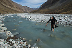 Snow Leopard (Panthera uncia) biologist, David Cooper, crossing river, Sarychat-Ertash Strict Nature Reserve, Tien Shan Mountains, eastern Kyrgyzstan