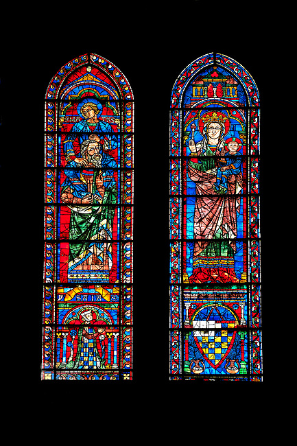 Medieval Window of the South Transept of the Gothic Cathedral of Chartres, France- Circa 1225-30. A UNESCO World Heritage Site. These windows were a donation of the Mauclerc family, the Counts of Dreux-Bretagne, who are depicted with their arms in the bases of the lancets above (right) is the Virgin Mary & Child and (left) is one of the four evangelists sitting on the shoulders of a Prophet - a rare literal illustration of the theological principle that the New Testament builds upon the Old Testament.