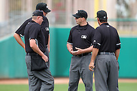 Umpires (L-R) Chad Whitson, Jordan Baker, Stephen Barga, and Barry Larson discuss a call during an Arizona Fall League game between the Mesa Solar Sox and Salt River Rafters at HoHoKam Park on November 4, 2011 in Mesa, Arizona.  Mesa defeated Salt River 12-10.  (Mike Janes/Four Seam Images)