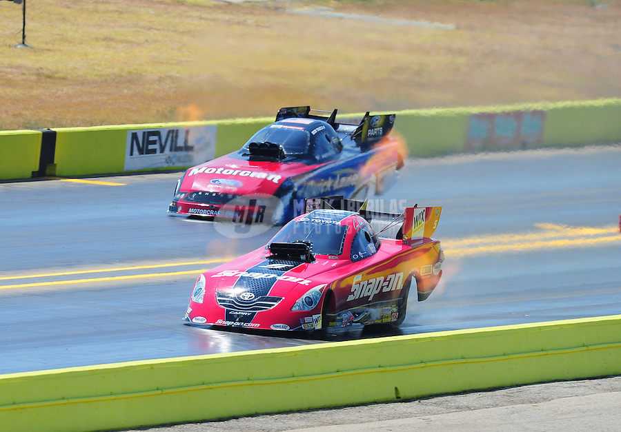 Sept. 25, 2011; Ennis, TX, USA: NHRA funny car driver Cruz Pedregon (near lane) races alongside Bob Tasca III during the Fall Nationals at the Texas Motorplex. Mandatory Credit: Mark J. Rebilas-