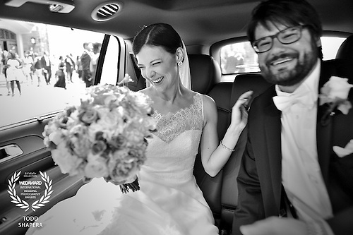 Bride and Groom celebrate in their limo outside Church