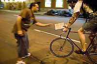 3 July 2005 - New York City, NY, USA - A rider arrives, manifest in hand, at an alleycat checkpoint manned by Richard (L) on 43rd street in New York City, USA, July 3rd 2005. Alleycats are urban cycle races held informally - without notification of the authorities - on open roads and in real traffic, to simulate the messenger's working conditions. Photo Credit: David Brabyn<br />