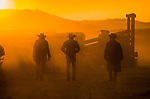 Cowboys walk back into camp after tending to the livestock at sunrise during the annual Reno Rodeo cattle drive which brings the livestock for use in the rodeo into town.