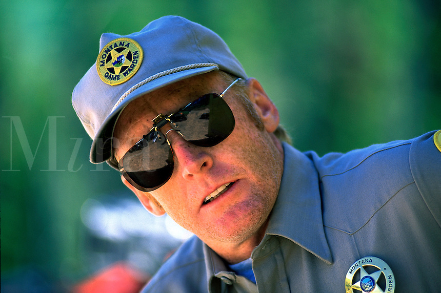 Portrait of a male Montana Game Warden in uniform clothing and sunglasses.