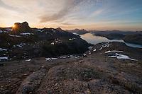 Midnight sun shines over distant mountains from summit of Hestræva, Flakstadøy, Lofoten Islands, Norway