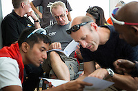 26 SEP 2013 - LANDS END, GBR - Paul Parrish (back centre) studies the race route maps at the race briefing before the start of the Enduroman 2013 Lands End to London to Dover ultra triathlon at Lands End, Sennen, Cornwall, Great Britain (PHOTO COPYRIGHT © 2013 NIGEL FARROW, ALL RIGHTS RESERVED)